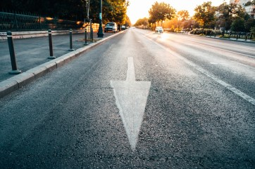 Arrow on road pointing at viewer during early morning. This image is meant to portray pursuing behaviors in Emotionally Focused Couples Therapy.