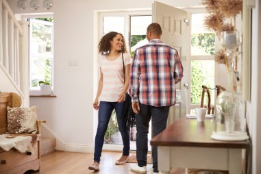 Bi-racial couple greeting one another at the front door. This image is meant to portray how couples connect from an Emotionally Focused Couples Therapy Intensive in Connecticut or an Emotionally Focused Couples Therapy Intensive in Massachusetts.