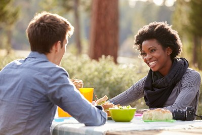 Bi-racial couple happily talking over a meal outside. This image is meant to portray emotional connection that occurs after attending an EFT couples retreat in New England or an EFT couples retreat in Massachusetts.