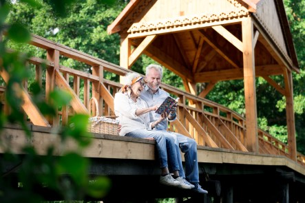 Empty nest couple relaxing together on a bridge and looking at an album. This image is meant to portray the communication skills and connection a couple has after attending a marriage seminar in New England or a marriage retreat in New England.