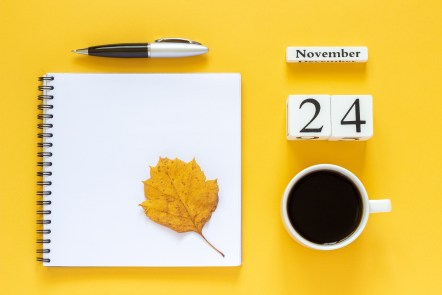 Notebook and coffee with calendar date on bright yellow background, This image is meant to portray date a hurting couple is planning to attend a couples therapy retreat in Maine, a couples therapy retreat in Connecticut, or couples therapy retreats in Massachusetts.