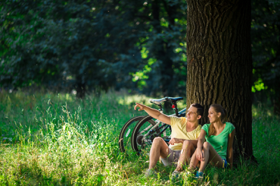 Couple who bike resting together at base of tree. This image meant to signify falling in love and knowing how to communicate due to attending a Hold Me Tight Workshop for Couples or a Private Couples and Marriage Retreat.