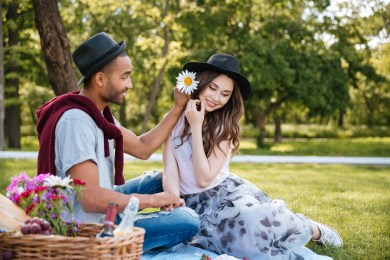 Bi-racial couple eating picnic in park with smiles. This image is meant to portray how you get relationship help fro attending Emotionally Focused intensive couples therapy in New England.