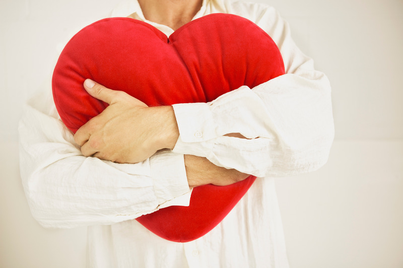 Man squeezing heart pillow. This is meant to symbolically portray holding a relationship dear, such as happens with emotionally focused intensive couples therapy in Massachusetts, New England.
