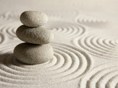 Stack of three stones on sand background. Signifies emotional balance after receiving relationship help for lesbian couples in the form of emotionally focused couples therapy intensive in Massachusetts..