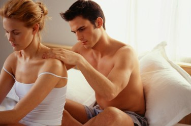Couple sitting in bed, man massaging shoulders of a woman. Signifies use of touch for connection in lgbt relationships, a skill learned in marriage counseling retreats in new england..