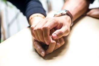 Couple holding hands over white table. This signifies improved emotional connection and better couples communication after attending a private marriage retreat in Massachusetts or a marriage retreat New England.