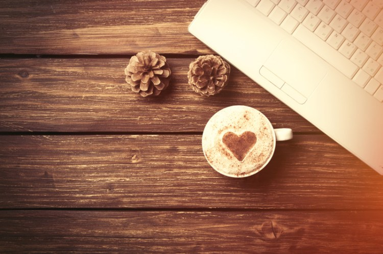 Cappuccino and laptop on wooden table. Meant to signify online hold me tight workshop, help for couples during covid, and marriage workshop near me..