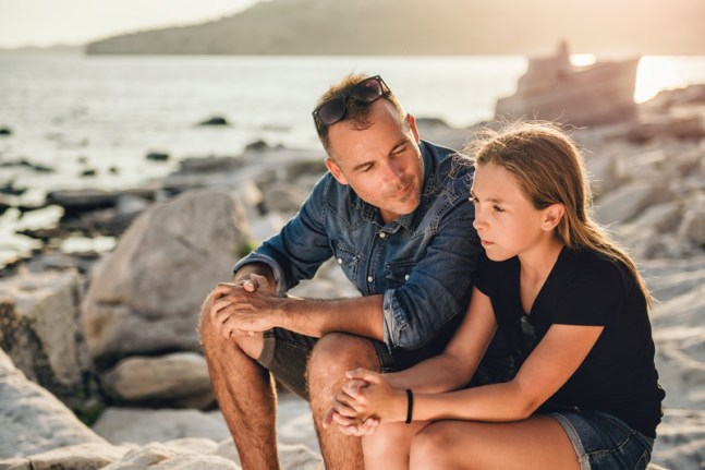 Father and daughter relaxing on a rocky beach by the sea and having time together. This signifies better connection and communication like what happens during marriage counseling retreats in Massachusetts.