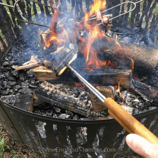 cooking 3 items over a campfire, pie iron, a hot dog and a marshmallow
