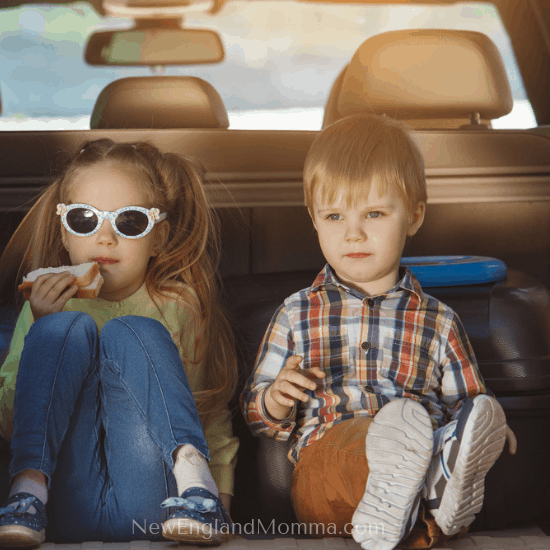 two kids sitting in the back of a car eating a pb&J
