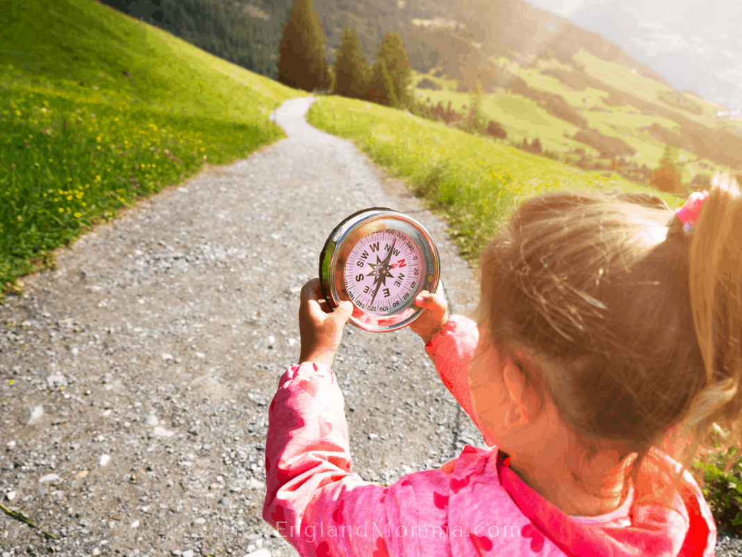 a little girl holding a compass while looking for letterboxes