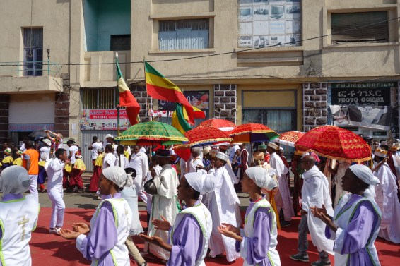 Children sing and dance in their uniforms as the main procession passes.