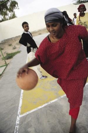 A young woman plays basketball at Socsa (Somaliland Culture and Sports Association)