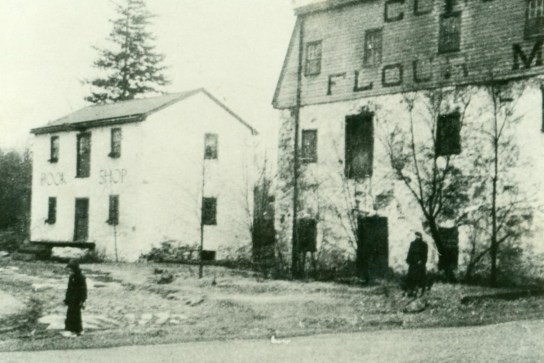 Black and white photograph of what is now the Archive building and the Newlin Grist Mill, with a woman standing in front of the mill and a child in the foreground.