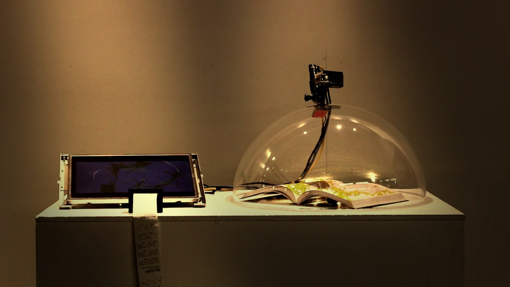 A book with fungus growing on it sits beneath and camera, connected to a computer