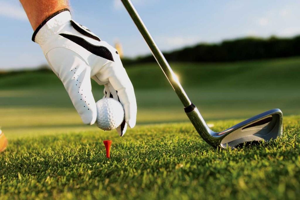 Golfer teeing ball