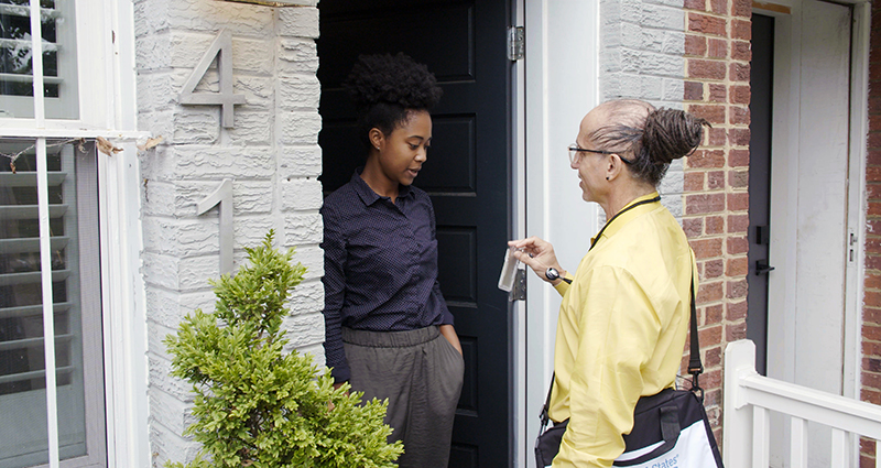 picture shows census worker at front door of home displaying his badge to homeowner