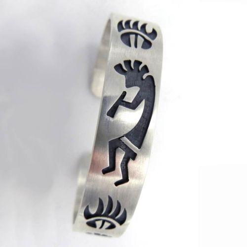 This traditional Hopi overlay bear paw and kokopelli cuff bracelet showcases alternating kokopellis and bear paws.