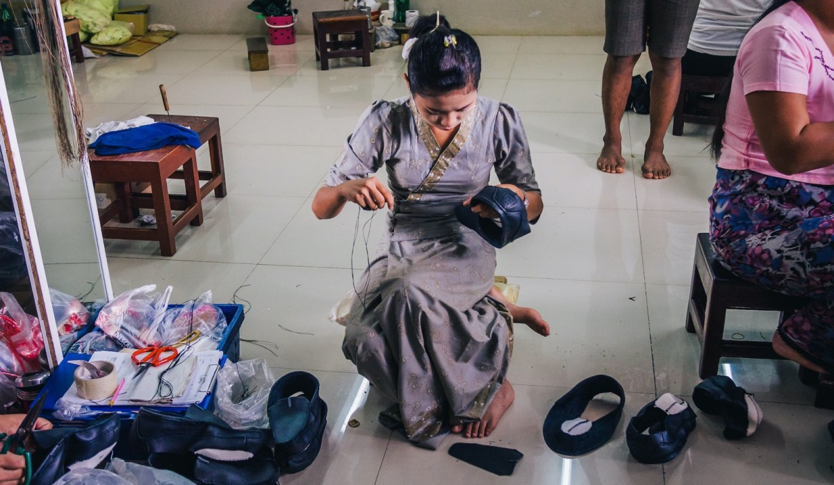 Burmese female migrant workers sewing or stitching leather shoes in footwear production line of factory in Sankhlaburi, Kanchanaburi, Thai-Burma border province.