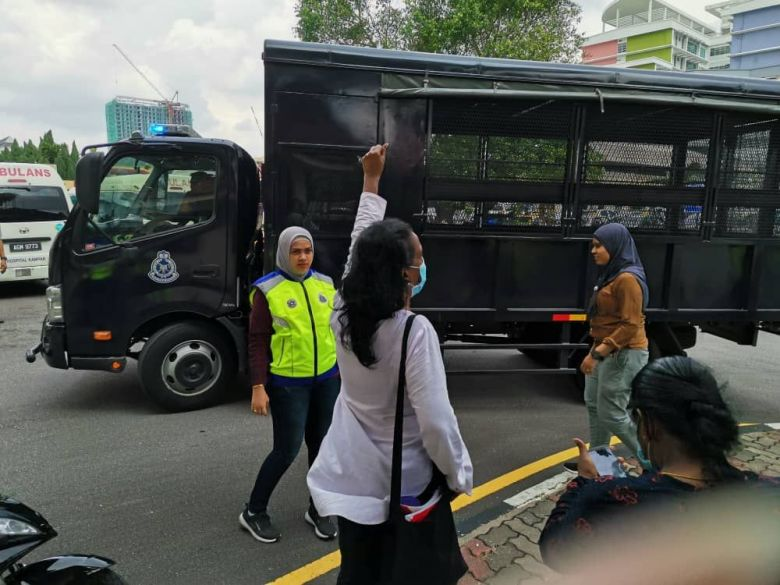 Police arrest Saras (in the white shirt) and other protestors outside Hospital Ipoh on 2 June 2020.