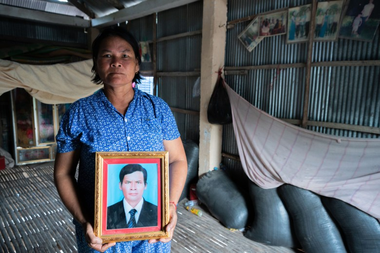 Kat Chang poses for a portrait in her home with a picture of her late husband Toun Sarith, who died of rabies.
