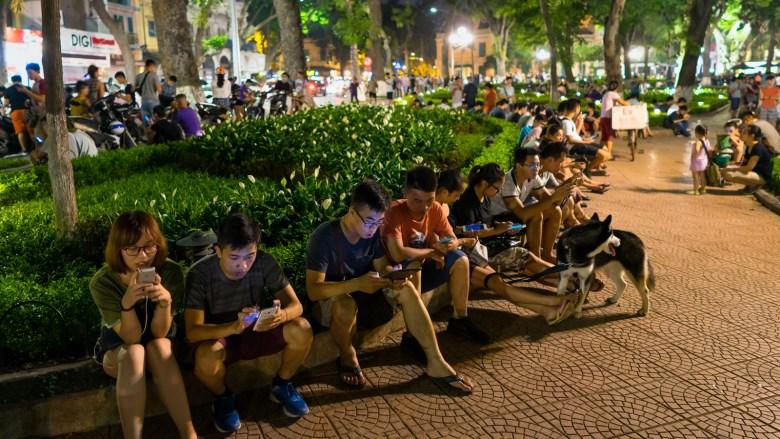 Teenagers use smartphones in a Hanoi park in 2016. (Vietnam Stock Images/Shutterstock)
