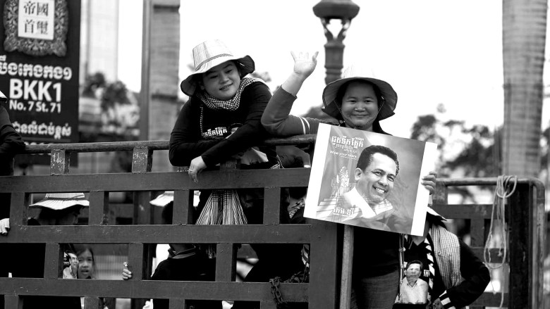 Two women hold up a photo of Kem Ley at his funeral.
