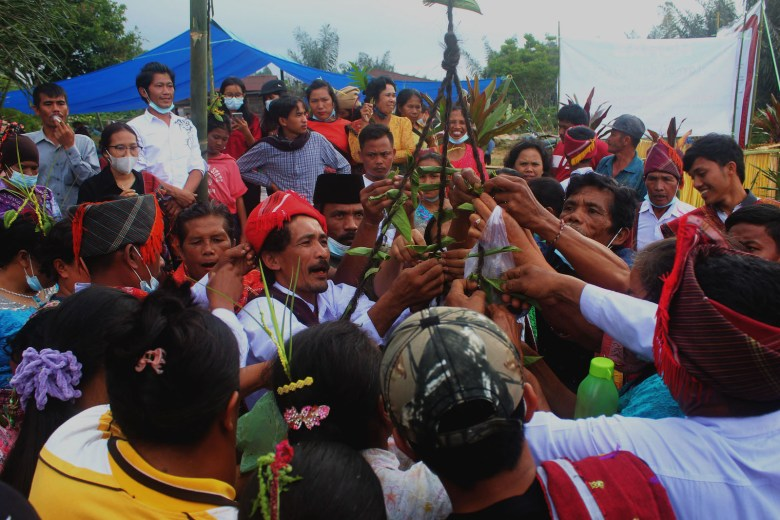 Spiritual leaders from the indignenous Sihaporas community conclude a traditional ritual by hoisting a woven betel leaf ornament above villagers' heads in May 2021.