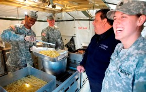 New Jersey Governor Chris Christie talks with New Jersey National Guard cooks Specialist Jerel Frayer, Sergeant Richard Pretto and Sergeant Sarah Zadoyko while they prepare food for emergency personnel and victims of Hurricane Sandy at a relief center in Sea Bright, New Jersey, November 9, 2012, in this handout photo courtesy of the governor's office. REUTERS/New Jersey Governor's Office/Tim Larsen/Handout (UNITED STATES - Tags: ENVIRONMENT DISASTER MILITARY POLITICS) FOR EDITORIAL -- USE ONLY. NOT FOR SALE FOR MARKETING OR ADVERTISING CAMPAIGNS. THIS IMAGE HAS BEEN SUPPLIED BY A THIRD PARTY. IT IS DISTRIBUTED, EXACTLY AS RECEIVED BY REUTERS, AS A SERVICE TO CLIENTS