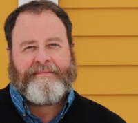 headshot of a man with a graying beard in front of a mustard yellow house