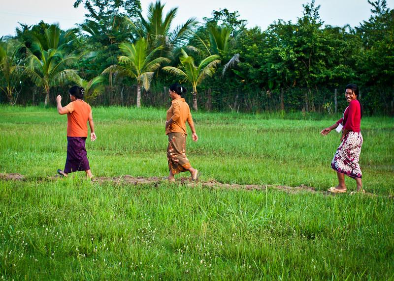 Women cross a flooded field