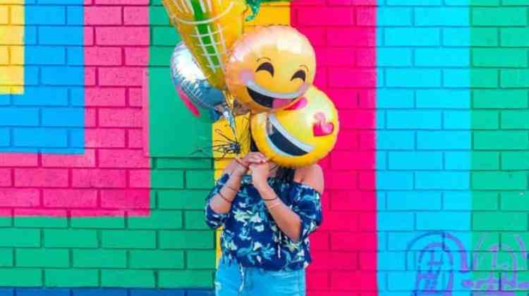 Woman covering her face with balloons with smiley faces
