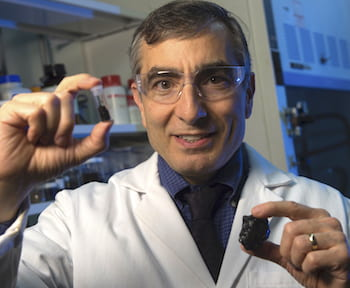 Rice University chemist James Tour holds coal and a vial of coal-derived graphene quantum dots. The dots have been modified for use as an effective antioxidant. (Credit: Jeff Fitlow/Rice University)