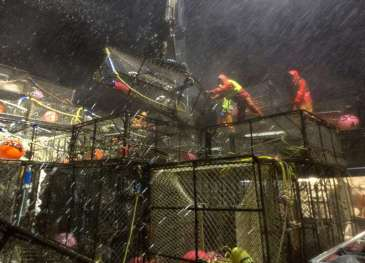 Crew members aboard the crab boat Arctic Hunter are nailed with spray flying over the bow as they maneuver crab pots in the stormy Bering Sea.
