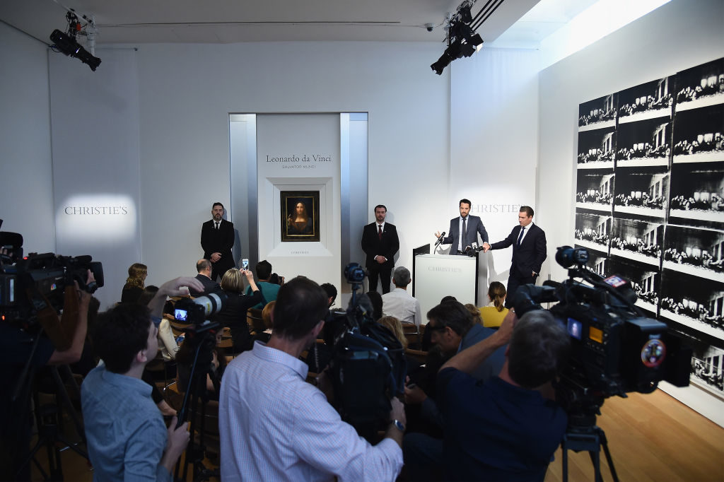 Loic Gouzer [center] speaks as Christie's unveils Leonardo da Vinci's <em>Salvator Mundi</em> with Andy Warhol's <em>Sixty Last Suppers</em> at Christie's New York on October 10, 2017 in New York City. Photo by Ilya S. Savenok/Getty Images for Christie's Auction House.