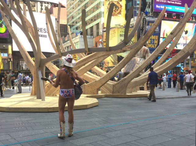 The famed Naked Cowboy plays in front of Mel Chin's Wake in Times Square. Image courtesy Ben Davis.