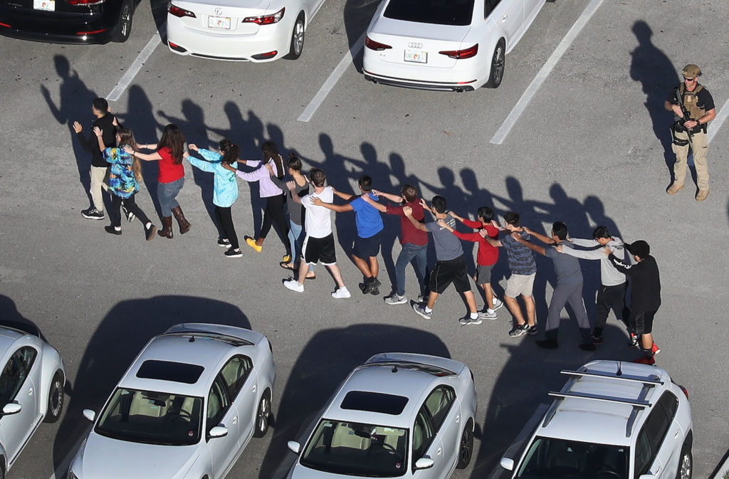 People are brought out of the Marjory Stoneman Douglas High School after a shooting at the school that reportedly killed and injured multiple people on February 14, 2018 in Parkland, Florida. Photo by Joe Raedle/Getty Images.