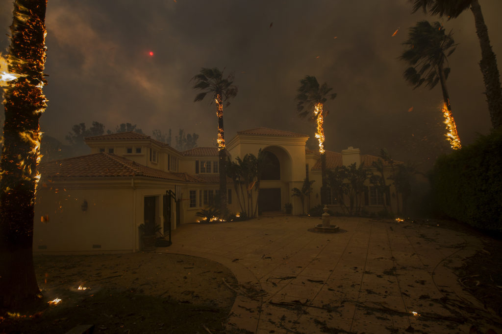 Embers falls from burning palms and the sun is obscured by smoke as flames close in on a house at the Woolsey Fire on November 9, 2018 in Malibu, California. Photo by David McNew/Getty Images.