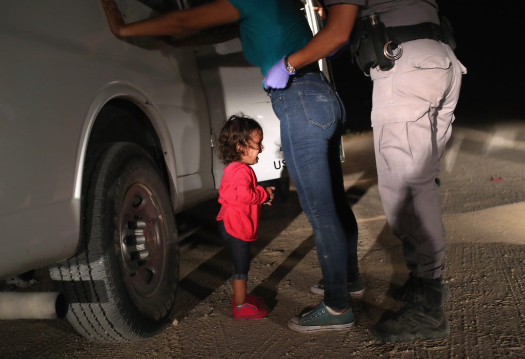 A two-year-old Honduran asylum seeker cries as her mother is searched and detained near the U.S.-Mexico border on June 12, 2018 in McAllen, Texas. Photo by John Moore/Getty Images.