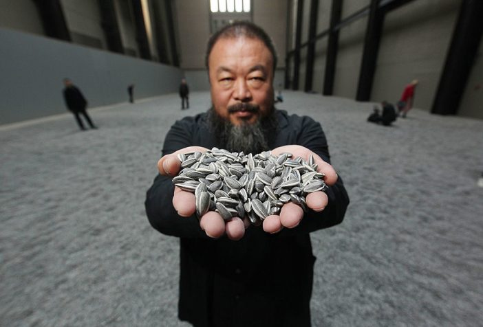 Chinese Artist Ai Weiwei holds some seeds from his installation Sunflower Seeds at Tate Modern in 2010. Photo by Peter Macdiarmid/Getty Images.