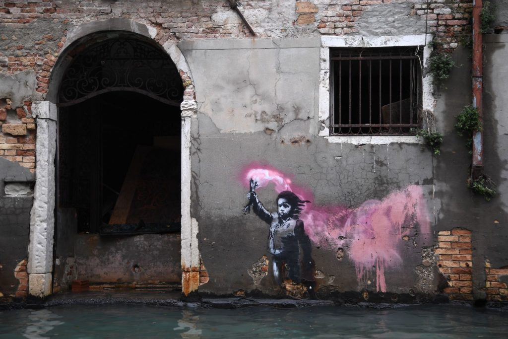 An artwork by street artist Banksy portraying a migrant child wearing a lifejacket and holding a neon pink flare pictured during the November 13, 2019 floods in Venice. Photo by Marco Bertorello/AFP via Getty Images.An artwork by street artist Banksy portraying a migrant child wearing a lifejacket and holding a neon pink flare pictured during the November 13, 2019 floods in Venice. Photo by Marco Bertorello/AFP via Getty Images.