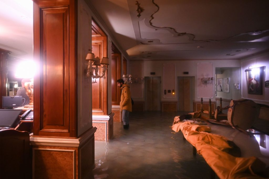 A man stands in a flooded room of the Gritti Palace during the floods on November 12 in Venice. Photo by Marco Bertorello/AFP via Getty Images.