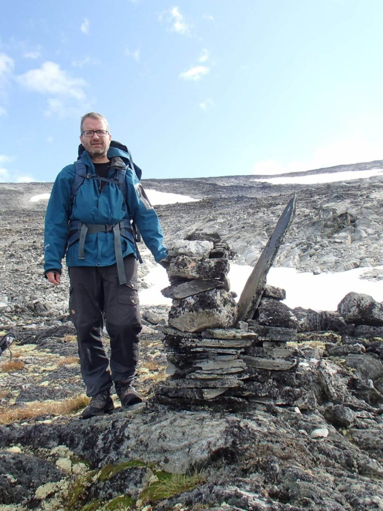 An archaeologist with one of the stone cairns marking the mountain pass at Lendbreen. The light-colored rocks in the background were covered with snow and ice until recently. Photo by James Barrett, University of Cambridge.