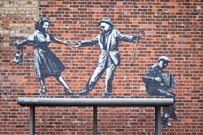Uma obra de grafite de um casal dançando ao som de um acordeonista em Great Yarmouth é uma das várias possíveis novas obras de Banksy na costa leste da Inglaterra. Foto de Justin Tallis / AFP via Getty Images.
