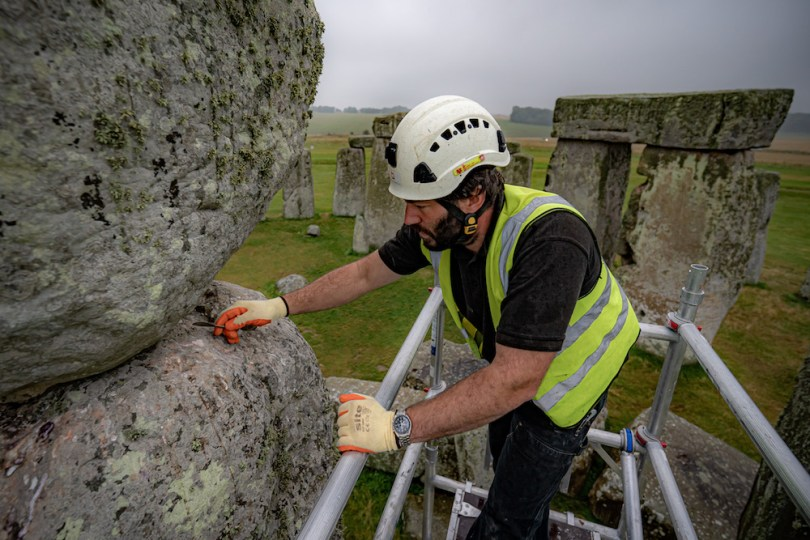 Conservator James Preston uses a pointing spoon atop scaffold erected inside the stone circle at Stonehenge as specialist contractors from SSH Conservation repair defects from previous repairs, carried out the 1950's, on a trilithon in the stone circle and carry out vital conservation work at Stonehenge, Wiltshire. Picture date: Tuesday September 14, 2021. (Photo by Ben Birchall/PA Images via Getty Images)