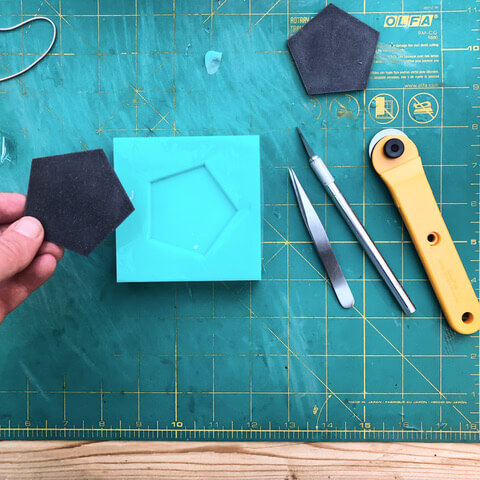 Black geometric shape with tools on a cutting mat.