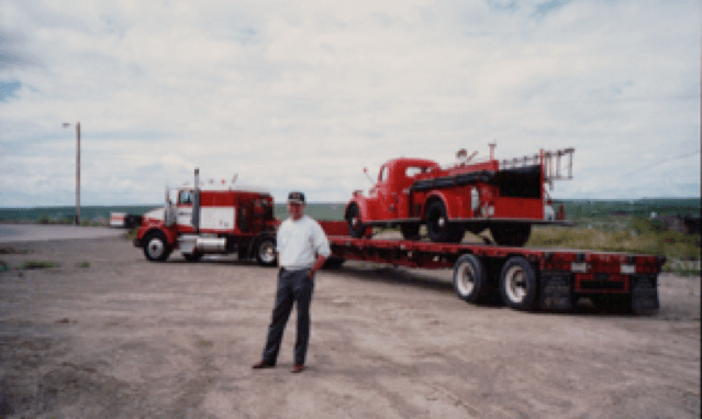 Jim stands in front of a semi-truck and flat-deck trailer with an antique firetruck on it