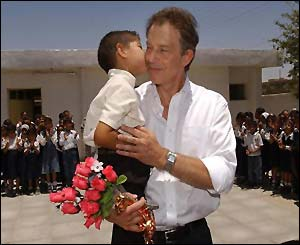 The prime minister gets a kiss from a young Iraqi