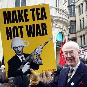 Photo of a man holding a placard saying 'Make Tea, Not War'